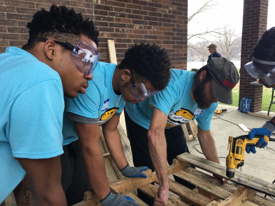 <p><em>Jay (left), Divad and Ruth (far right) work with Build Corps mentor Bryan Huber on their bench.</em></p>